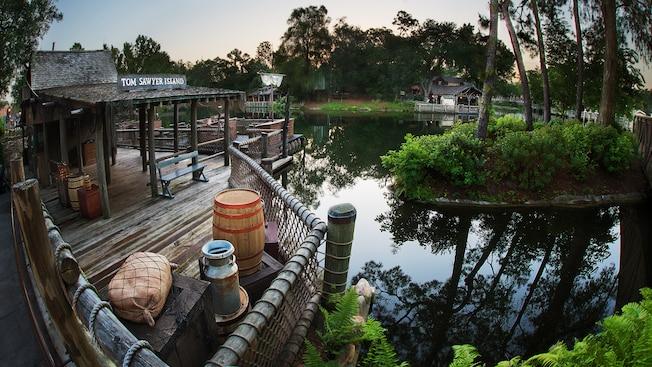 Um cais de madeira onde os visitantes embarcam em jangadas pelo Rivers of America para a atração Tom Sawyer Island