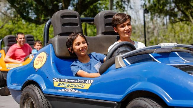 Dois irmãos dirigem um carro na Tomorrowland Speedway no Magic Kingdom Park