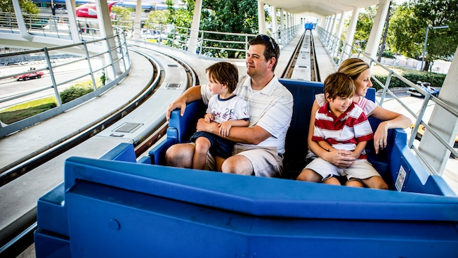 A mom and dad, each holding a young son, ride Tomorrowland Transit Authority PeopleMover