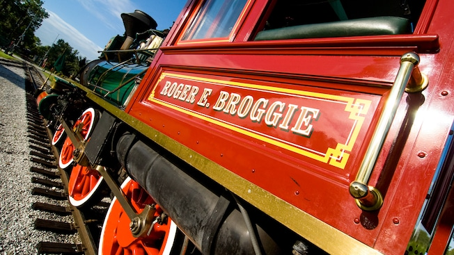Angled view of a red steam engine with the name 'Roger E. Broggie' painted on it