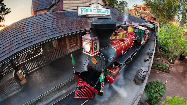 A train sits at the rustic Walt Disney World Railroad - Frontierland Station in Magic Kingdom park