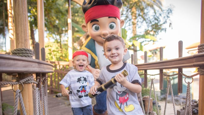 Two young boys, each holding a pirate spyglass, jog ahead of Jake, leader of the Never Land Pirates