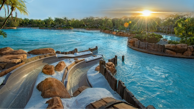 The sun peeks over trees, illuminating Bay Slides at Disney's Typhoon Lagoon water park