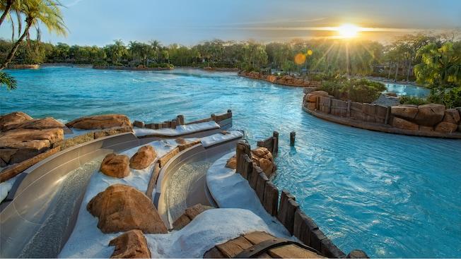 El sol aparece por encima de los árboles e ilumina Bay Slides en el parque acuático Disney's Typhoon Lagoon
