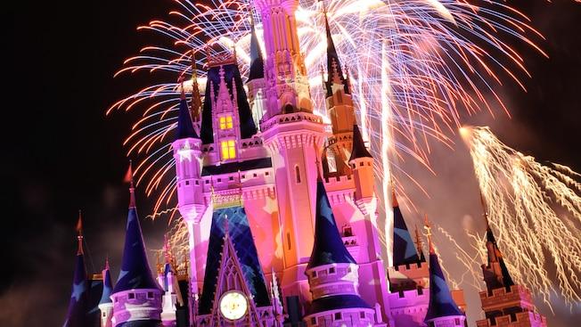 Nighttime fireworks illuminating the sky above Cinderella Castle