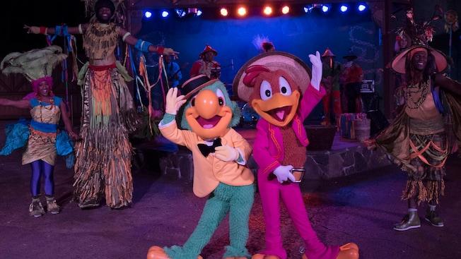 José y Panchito de The Three Caballeros bailan con otros bailarines y artistas en zancos mientras una banda toca en vivo