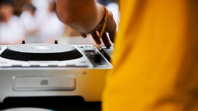 DJAnaan utilise sa main gauche pour passer des chansons sur une table de lecture et une console de mixage lors d'une fête dans la rue