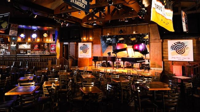 Interior de Jellyrolls, un restaurante con un escenario con duelos de pequeños pianos de cola