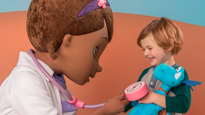 Doc McStuffins uses a stethoscope to check the heartbeat of a smiling child holding a plush dinosaur