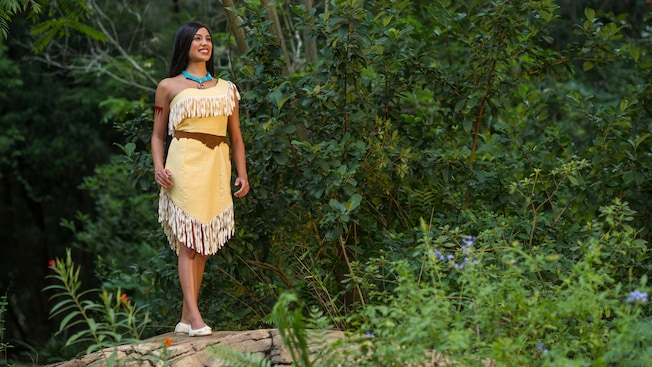 Pocahontas stands in a wooded area at Meet Pocahontas on Discovery Island Trail