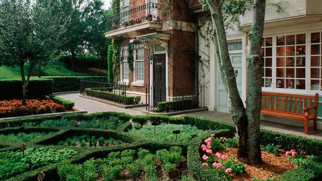 An English themed landscape with a manicured garden next to a brick building with ornate railings