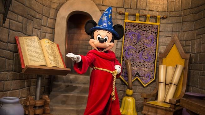 Mickey the Sorcerer parado con una mano extendida en un área decorada como un castillo, con un libro de hechicero, pergaminos y una escoba de aprendiz