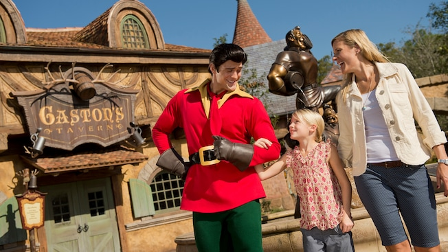 Gaston welcomes a little girl and her mother at the entrance of Gaston's Tavern