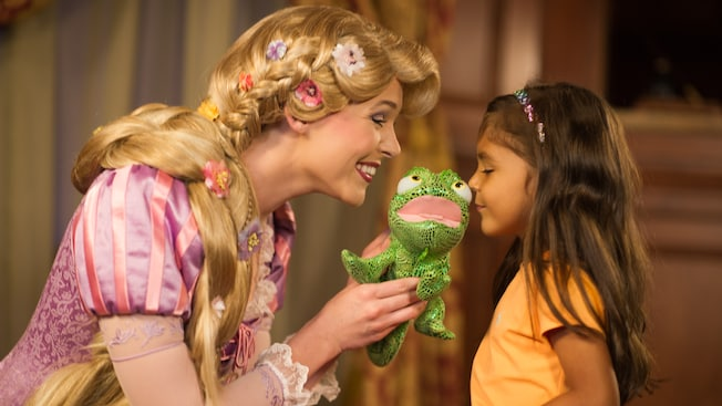 Rapunzel holds a toy frog for a girl to kiss at Princess Fairytale Hall in Fantasyland