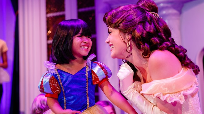Una niña pequeña vestida como Snow White sonríe mientras se encuentra con Belle.