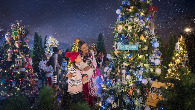 Multiple families look at decorated Christmas trees that have signs on them that read Little Mermaid and Marry Poppins