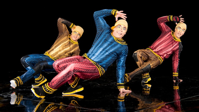 Three male break dancers, with their faces painted, perform onstage