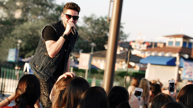 Drey C sings into a microphone at an outdoor venue in front of an audience