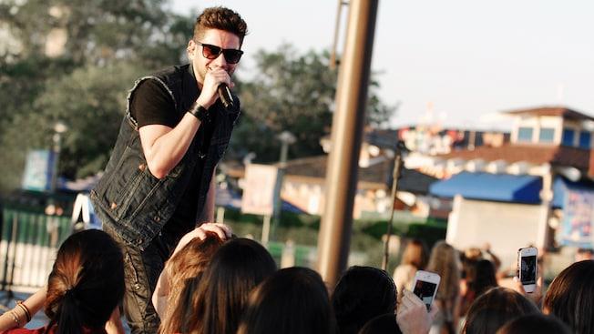 DreyC chante en public dans un microphone lors d'un événement en plein air