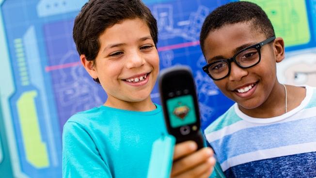 Deux jeunes garçons regardent un dispositif semblable à un téléphone cellulaire qui guide les visiteurs dans une quête interactive à Epcot