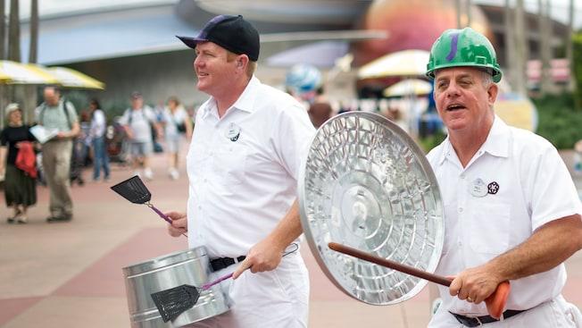 Dos miembros del grupo de percusión JAMMitors golpean una vasija y una tapa de un tacho de basura en Epcot