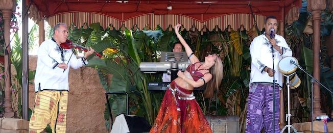 Una mujer baila sobre un escenario mientras 3hombres tocan instrumentos cerca