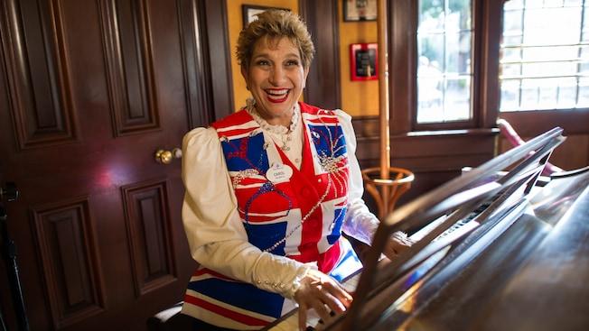 Una pianista del bar sentada al piano con un chaleco inspirado en la bandera británica