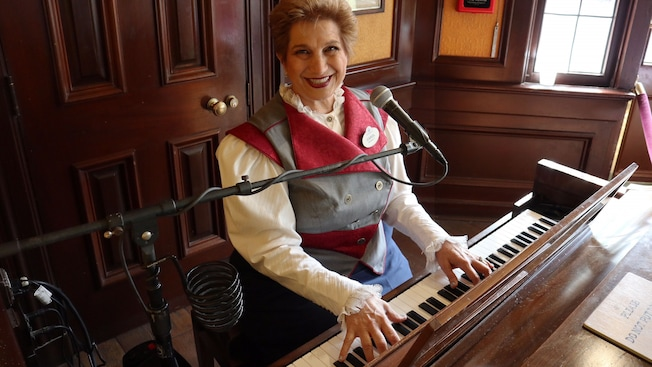 Un Miembro del Elenco sonríe mientras toca el piano frente a un micrófono