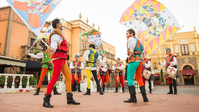 Men in colorful outfits wave multicolored flags as they are backed by live musicians
