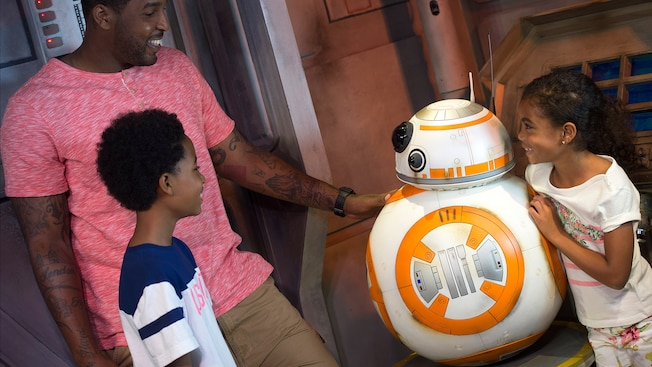 Pai, filho e filha encontram o B B 8, o leal droide do filme Star Wars – The Force Awakens, no setor de segurança da Star Wars Launch Bay