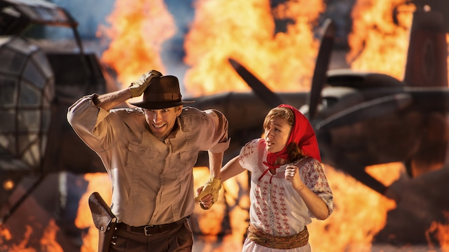 Indiana Jones and Marion run on a fiery set of the Indiana Jones Epic Stunt Spectacular