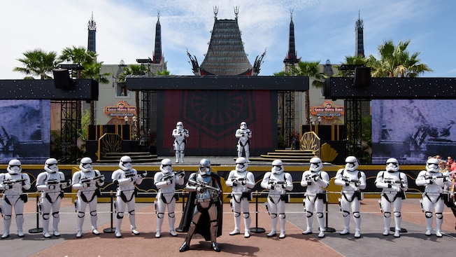 Na Animation Courtyard do Disney's Hollywood Studios, a Captain Phasma com seu blaster a postos e uma fileira de Stormtroopers Imperiais em guarda em frente a mais 2 Stormtroopers Imperiais enfileirados em um palco ao fundo