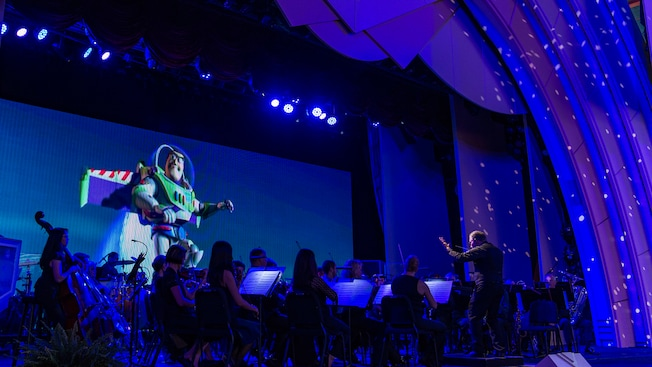 A projection of Buzz Lightyear from the hit Toy Story movies behind an orchestra