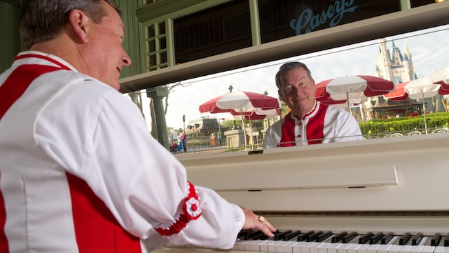 A piano player plays a piano at Casey's Corner with Cinderella's Castle reflected in a mirror