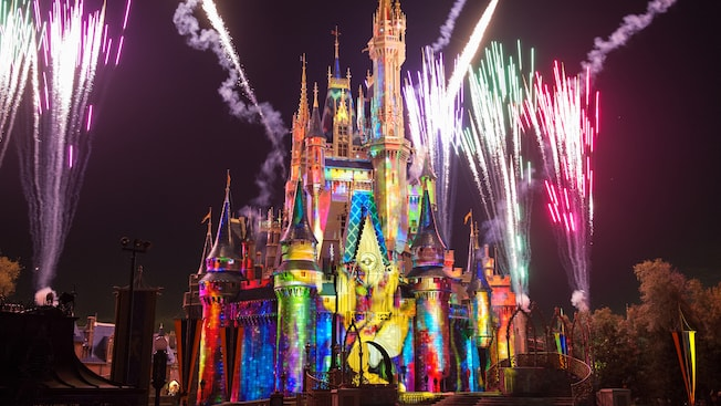 Vibrant art featuring Disney storytelling projected onto Cinderella Castle amid evening fireworks