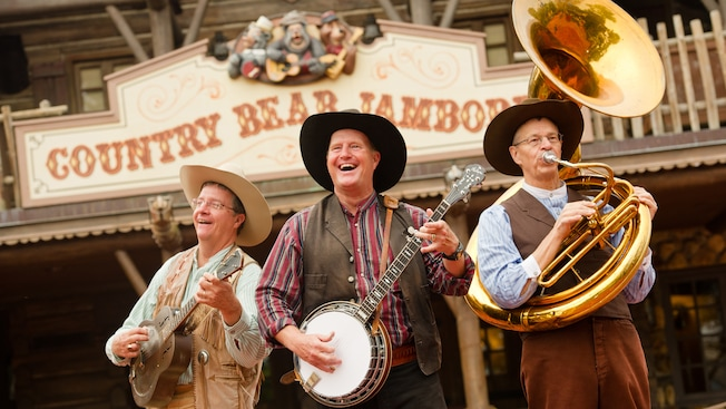 The 3 members of The Notorious Banjo Brothers and Bob band playing outside Country Bear Jamboree