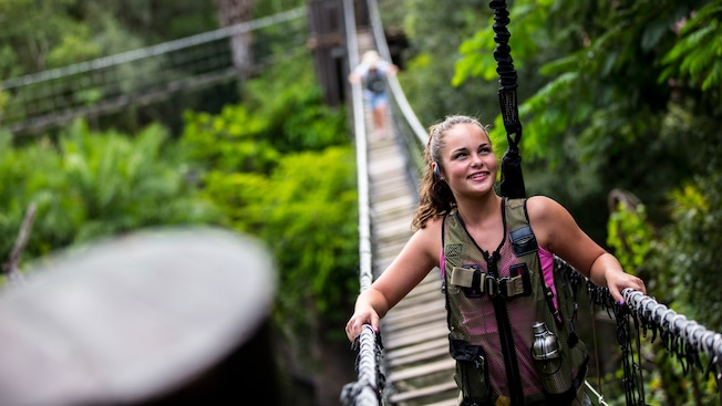 A teenaged girl wearing a safety-harness vest crosses a rope bridge on Wild Africa Trek