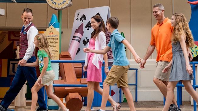 Une famille surexcitée sourit tout en suivant un guide VIP enthousiaste à ToyStoryMidwayMania!