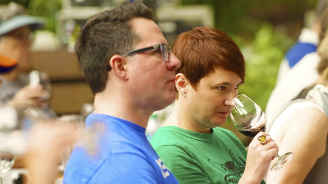 A female Guest sniffs a glass of wine among other Guests who in attendance at the Beverage Boot Camp Series