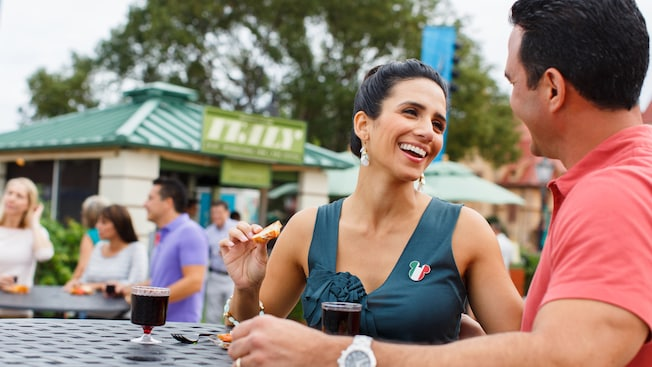 A couple enjoy appetizers and red wine outside the Italy marketplace