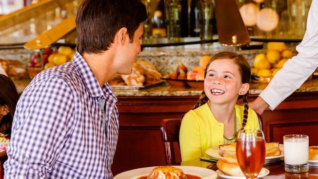 Una niña le sonríe a su padre mientras disfruta de un plato recién preparado en un evento de desayuno parisino