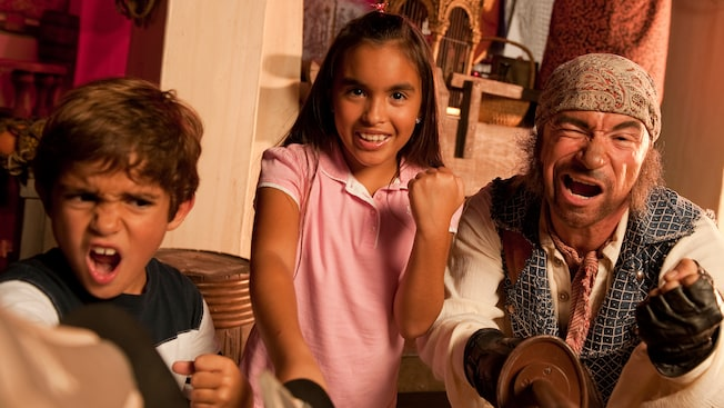 Menino e menina cerram os punhos em um grito de ataque sob a liderança de um pirata que empunha uma espada