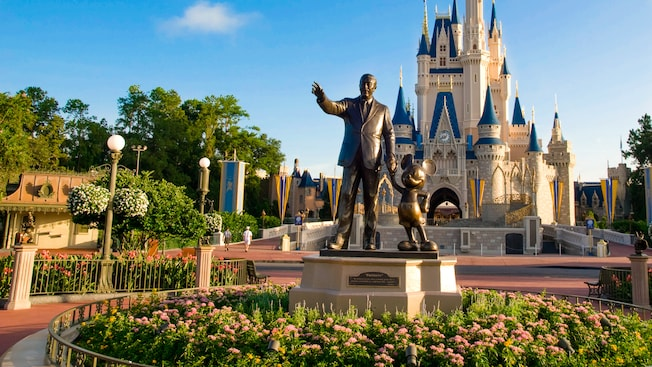 Partners statute of Walt Disney holding Mickey Mouse's hand in front of Cinderella Castle