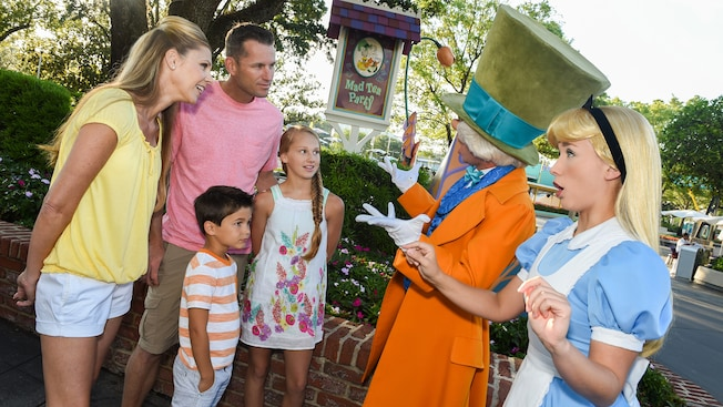 Una familia habla con Mad Hatter y Alice cerca de un letrero que dice Mad Tea Party