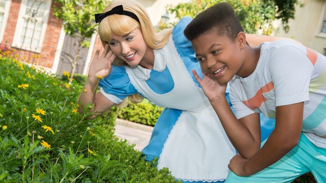 Alice from Disney's Alice in Wonderland listens to flowers with a young boy
