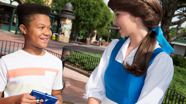 A young male Guest smiles while meeting Belle during a Character Greeting experience at Epcot