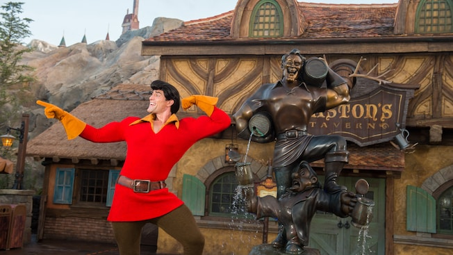 Gaston flexes while proudly posing by a statue of himself outside of Gaston's Tavern in Fantasyland