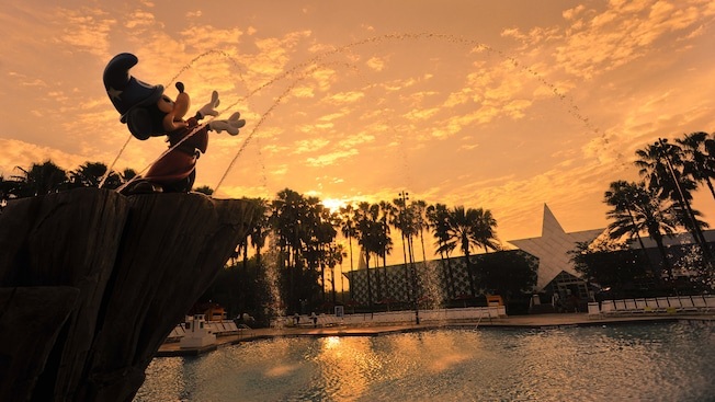 Silhouette de la fontaine Sorcerer Mickey sur un ciel de coucher de soleil à la piscine Fantasia du Disney All-Star Movies Resort