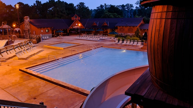 Partial view of barrel and waterslide at Meadow Swimmin' Pool next to kiddie pool after dark