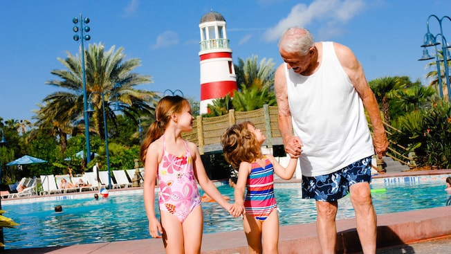 Un abuelo con sus dos nietas junto a una piscina en Disney's Old Key West Resort